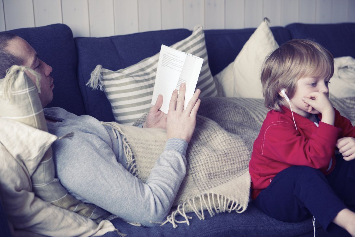 A reading man and a kid watching a movie in a sofa